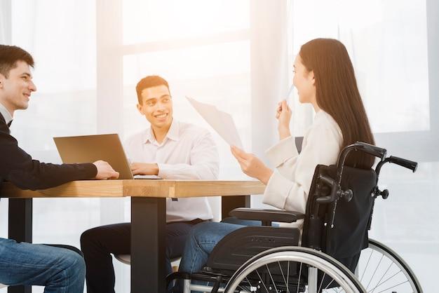 Incapacitado jovem empresária sentado na cadeira de rodas, discutindo com seu colega masculina no escritório
