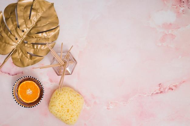 Incensos em garrafa de vidro; fruta laranja cortada ao meio; folha de monstera e pedra-pomes amarela no fundo texturizado rosa
