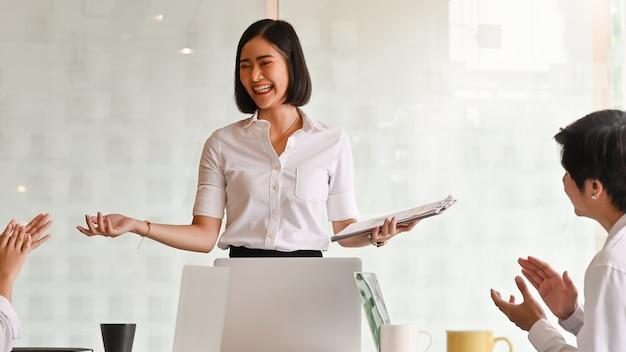 Incentivo de colega antes jovem empresária explicando sua idéia na sala de reunião.