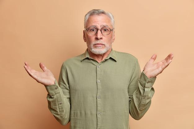 Incerto e intrigado, homem barbudo, maduro, de cabelos grisalhos, encolhe os ombros com hesitação, usa óculos e faz poses de camisa contra a parede marrom.