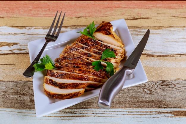 Incisão de frango assado com legumes, em um prato branco