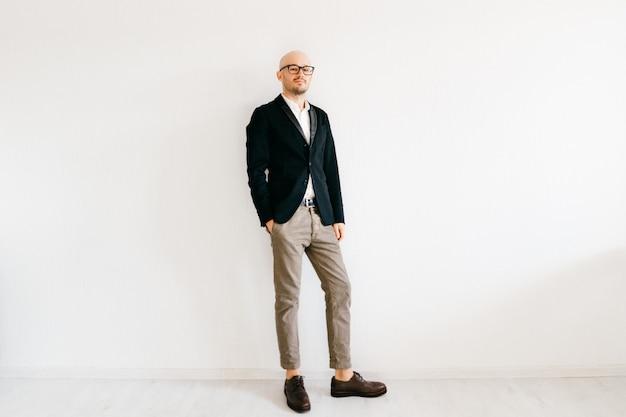 Incline o retrato macio do turno do empresário em roupas da moda italianas caras em pé dentro de casa