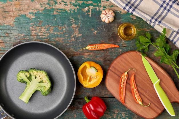 Inclua vegetais orgânicos frescos e frigideira no chão de madeira