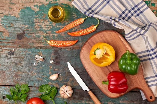 Inclua vegetais orgânicos frescos e tábua de corte de madeira no piso de madeira com cópia espaço de natureza morta