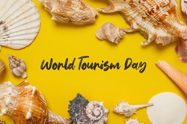 Incrição do dia mundial do turismo sobre fundo amarelo, com folhas de palmeira, concha e fundo plano de sapatos