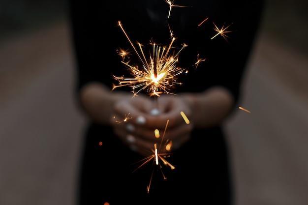 Incríveis estrelinhas festivas nas mãos de uma jovem