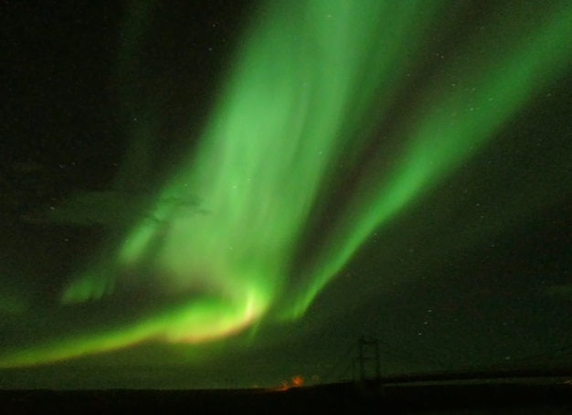 Incrível aurora boreal dançando sobre a ponte no parque nacional de vatnajokull, islândia