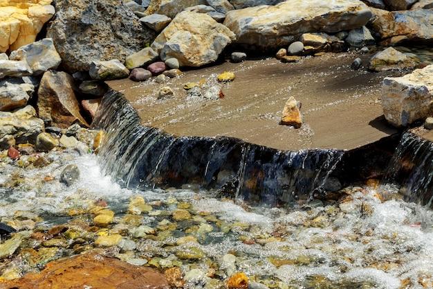Incrível cachoeira do lago azul com águas cristalinas entre madeiras verdes