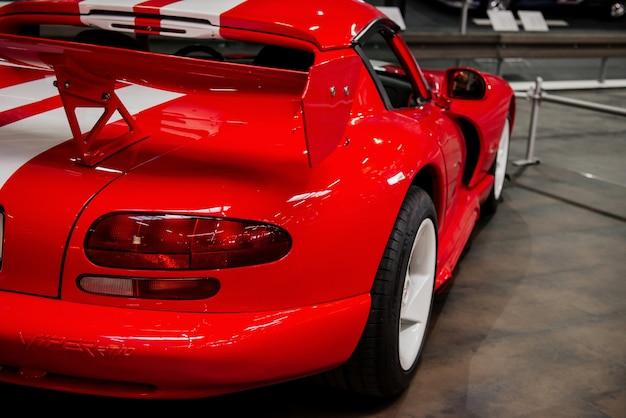 Incrível carro esporte vermelho com listras brancas estacionado dentro de casa