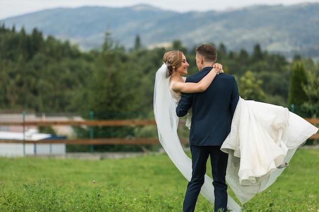 Incrível casal sorridente de casamento. linda noiva e noivo elegante.