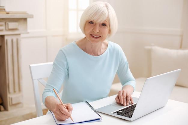 Incrível e inspiradora senhora inteligente sentada à mesa e escrevendo algo enquanto lia um relatório em seu laptop