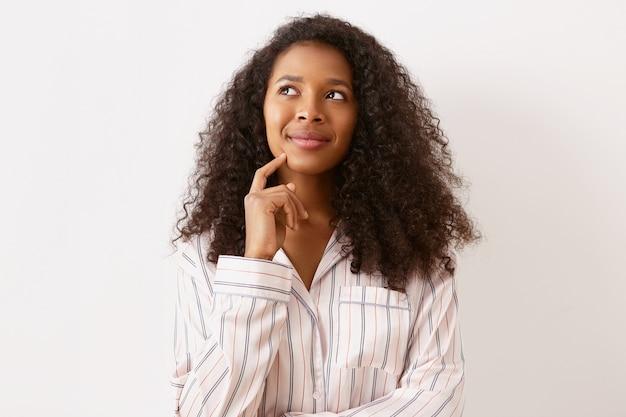 Incrível garota adorável de origem afro-americana com expressão facial pensativa e sonhadora, olhando para cima e sorrindo, segurando o dedo da frente no queixo, pensando sobre planos de férias e futuro emocionante