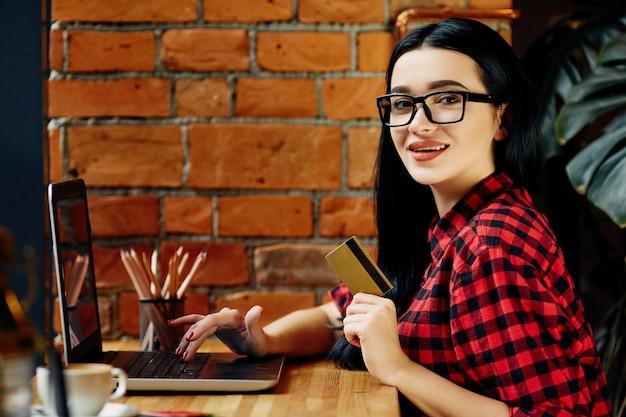 Incrível garota de cabelo preto, usando óculos, sentado no café com laptop, telefone celular, cartão de crédito e xícara de café, conceito freelance, compras online, vestindo camisa vermelha.