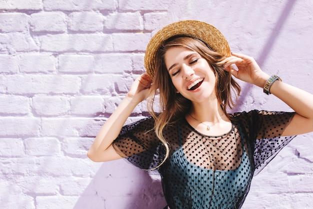 Incrível garota de cabelos compridos em roupas elegantes, curtindo um bom dia do lado de fora, de olhos fechados sob o sol