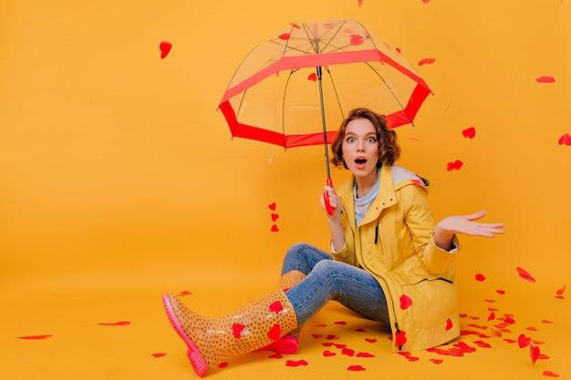 Incrível garota encaracolada com guarda-chuva expressando espanto durante a chuva de coração. foto de estúdio da adorável modelo feminino morena com sapatos de borracha, posando no dia dos namorados.