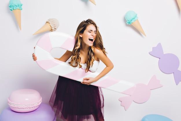 Incrível garota gulosa, rodeada de doces de brinquedo, se divertindo na festa e cantando. retrato de jovem em elegante vestido violeta segurando um grande bastão de doces