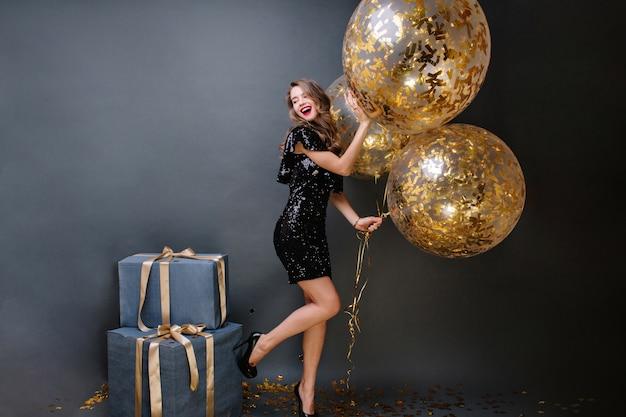 Incrível jovem elegante de salto alto, em vestido de luxo preto com grandes balões cheios de enfeites dourados. presentes, festa de aniversário, comemoração, sorriso, expressão de positividade.
