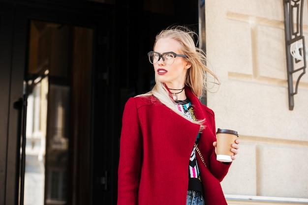 Incrível jovem mulher caucasiana, caminhando ao ar livre, bebendo café.