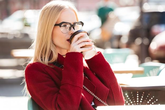 Incrível jovem mulher caucasiana, falando por telefone, bebendo café