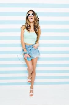 Incrível jovem mulher com cabelo longo morena encaracolado, de shorts jeans nos saltos, óculos de sol azuis, rindo na parede azul branca listrada. ouvir música com fones de ouvido, horário de verão.