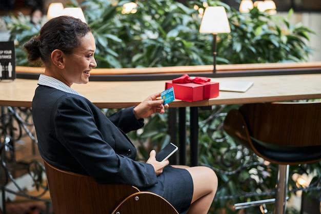 Incrível jovem mulher sentada semicerrada e com um sorriso no rosto enquanto faz compras online