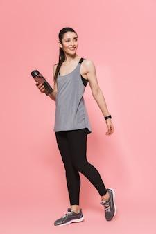 Incrível linda jovem bonita fitness mulher segurando uma garrafa com água potável isolada sobre a parede rosa