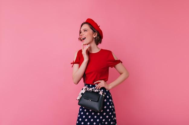 Incrível modelo feminino em roupa francesa, posando com a expressão do rosto animado. retrato interior de mulher europeia interessada com bolsa de couro preto.
