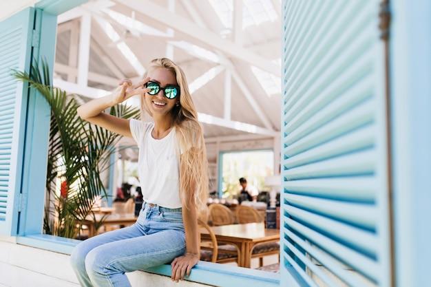 Incrível modelo feminino europeu em t-shirt branca, posando de óculos escuros e jeans azul cintilante.