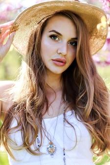 Incrível mulher jovem e atraente com cabelo comprido, chapéu, vestido de luz branca, aproveitando o dia ensolarado de primavera no jardim, em fundo de sakura florescendo.