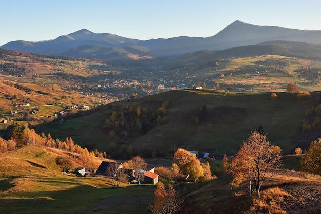 Incrível paisagem de manhã de outono nas montanhas com prados e árvores coloridas em primeiro plano e nevoeiro sob os pés.