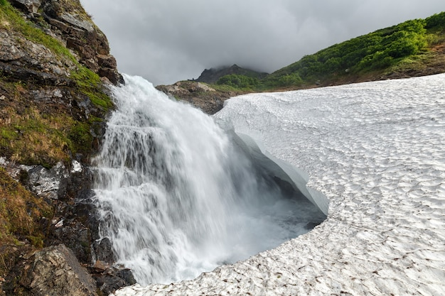 Incrível paisagem de montanha vista de verão da cachoeira caindo no campo de neve na cordilheira