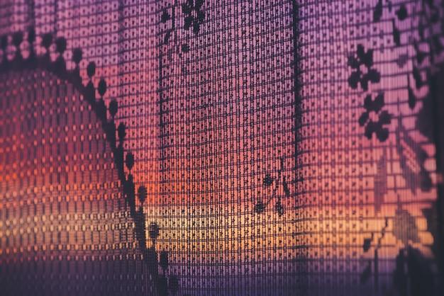 Incrível por do sol romântico na janela atrás de silhuetas de textura de tule. céu violeta laranja rosa maravilhoso amanhecer da janela através da cortina estampada. cosiness fundo do nascer do sol cênico. copie o espaço.