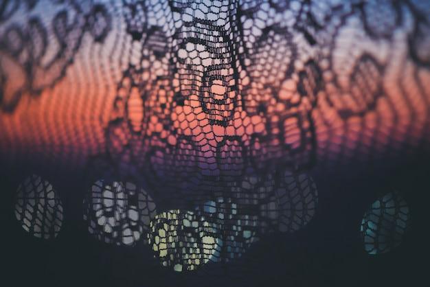 Incrível por do sol romântico na janela atrás de silhuetas de textura de tule.