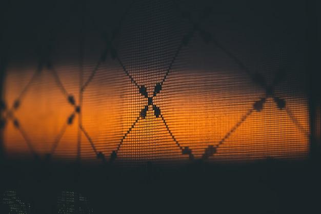 Incrível por do sol vívido romântico na janela atrás de silhuetas de textura de tule.