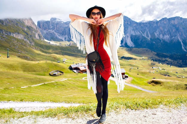Incrível retrato ao ar livre de mulher elegante boho posando em resort de luxo com vista para as montanhas de tirar o fôlego, experiência de viagem de férias.