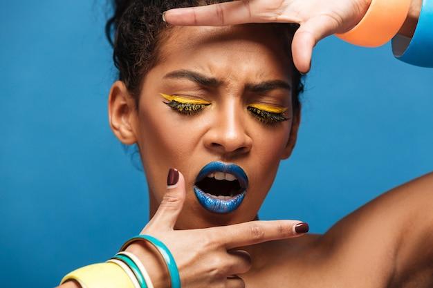 Incrível retrato de mulher afro-americana emocional com maquiagem brilhante e acessórios cobrindo o rosto com as mãos, parede azul