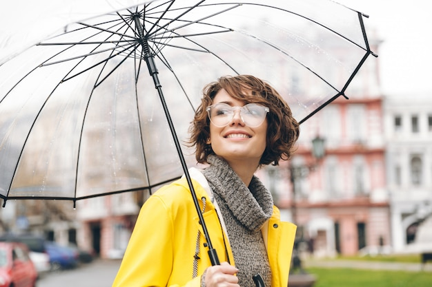 Incrível retrato de mulher feliz na capa de chuva amarela andando na cidade sob o guarda-chuva transparente durante o dia chuvoso frio