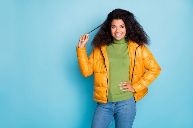 Incrível senhora de pele escura e cacheada com bom humor de primavera brincando com ondas onduladas, vestir um casaco de outono amarelo na moda jeans verde pulôver isolado parede azul