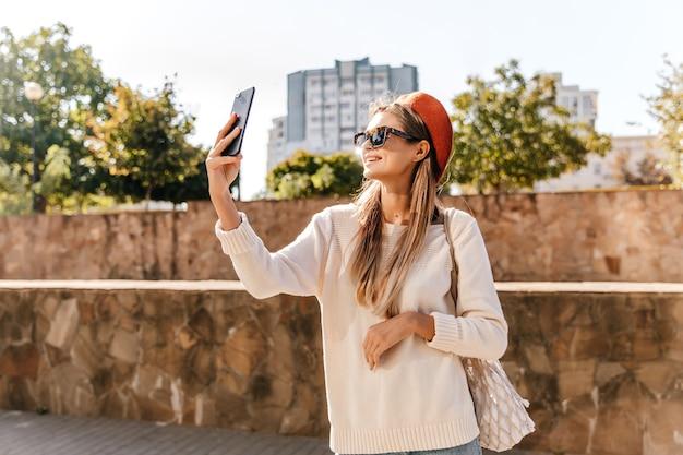 Incrível senhora francesa de camisa branca, fazendo selfie no fim de semana de outono. adorável garota deslumbrante na boina vermelha em pé na rua com o telefone.
