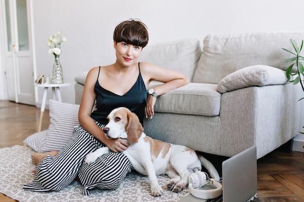 Incrível senhora morena usando elegante relógio de pulso posando ao lado do sofá acariciando o lindo beagle