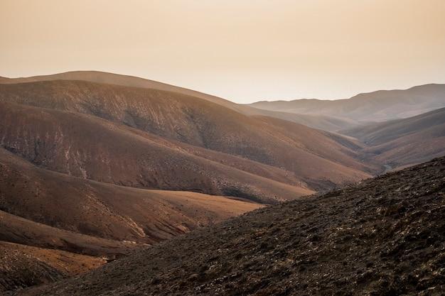 Incrível vale tranquilo bonito com montanhas vermelhas e céu alaranjado da manhã. lugar perfeito para o destino da viagem e descoberta alternativa de férias