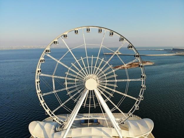Incrível vista aérea de cima por drone na capital do azerbaijão - baku. roda gigante na beira-mar do mar cáspio