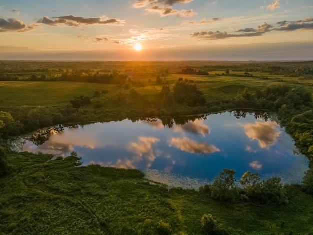 Incrivelmente belo pôr do sol ensolarado um pequeno lago no qual o céu e as nuvens se refletem
