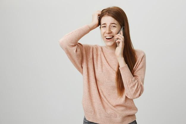 Indecisa e pensativa garota ruiva coçando a cabeça falando ao telefone, pensando
