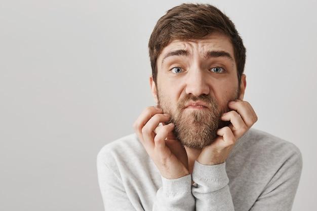 Indeciso e pensativo coçando a barba e parecendo complicado
