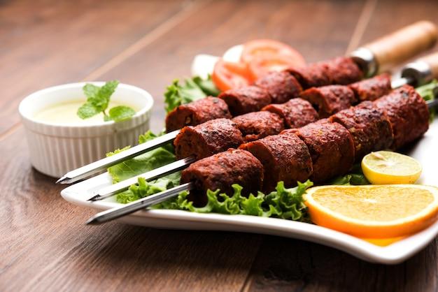 Indian mutton seekh kabab servido com salada verde, foco seletivo