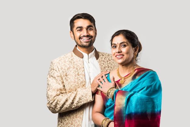 Indiana asiática velha mãe e filho adulto em roupas tradicionais em pé isolado sobre uma parede branca
