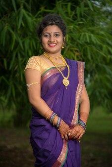 Indiana tradicional linda jovem em saree posando ao ar livre