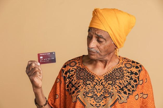 Indiano cético e misto segurando um cartão de crédito