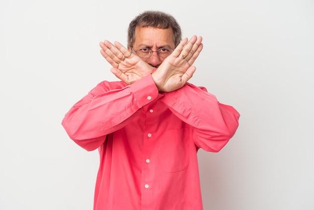 Indiano de meia idade isolado no fundo branco fazendo um gesto de negação